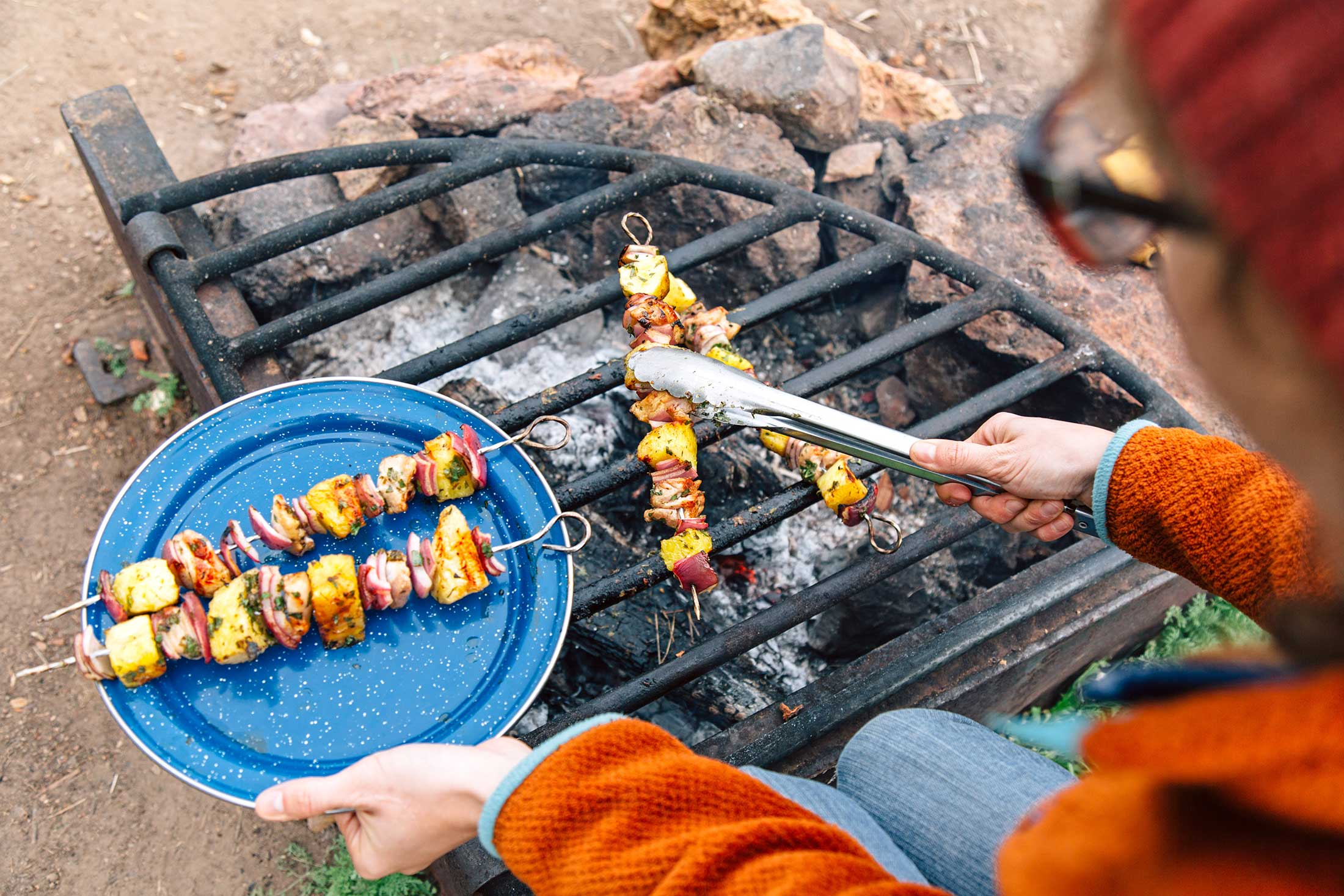 cooking pineapple chicken kebabs while camping