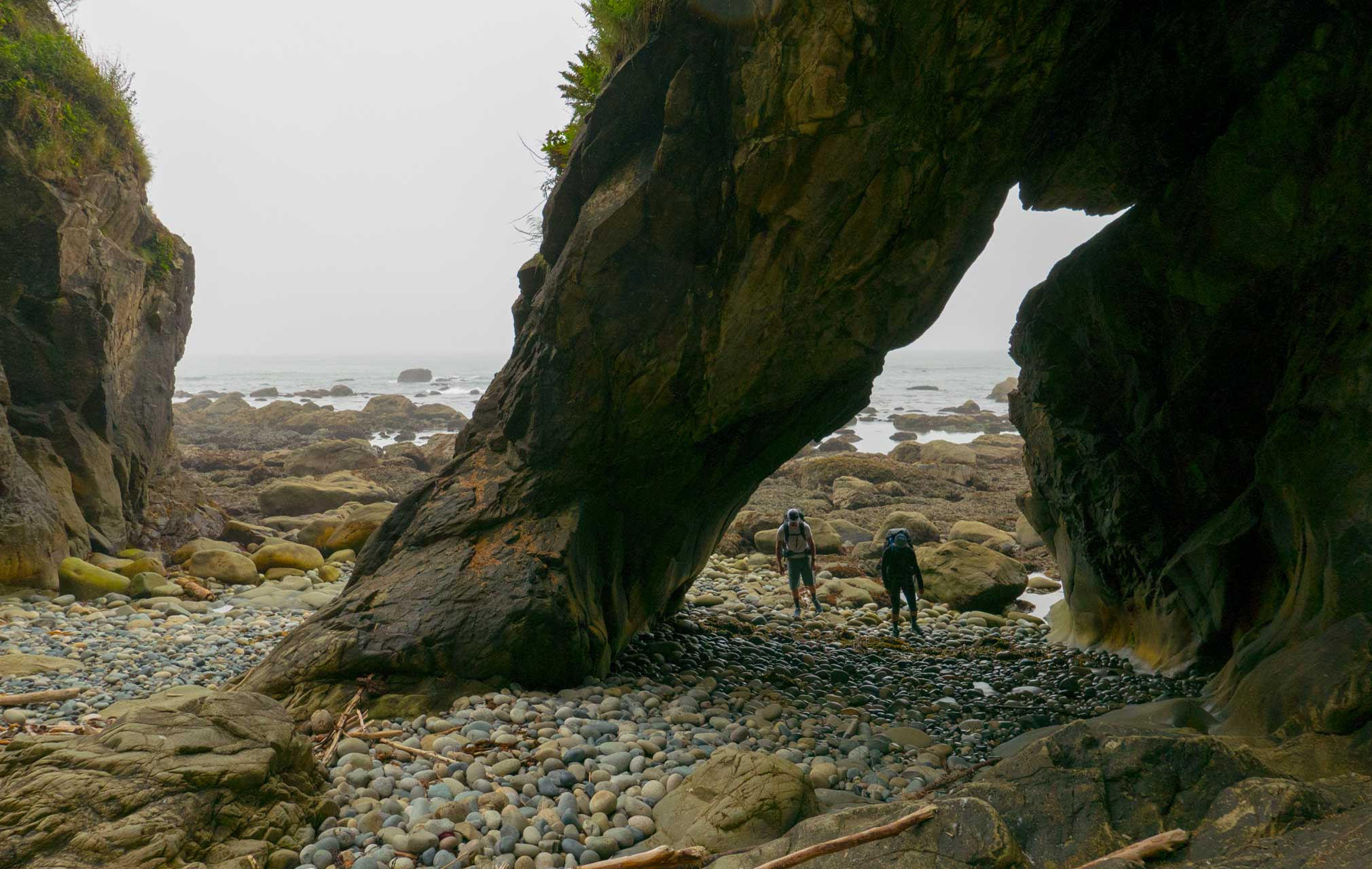 Passing through an arch while backpacking Olympic coast