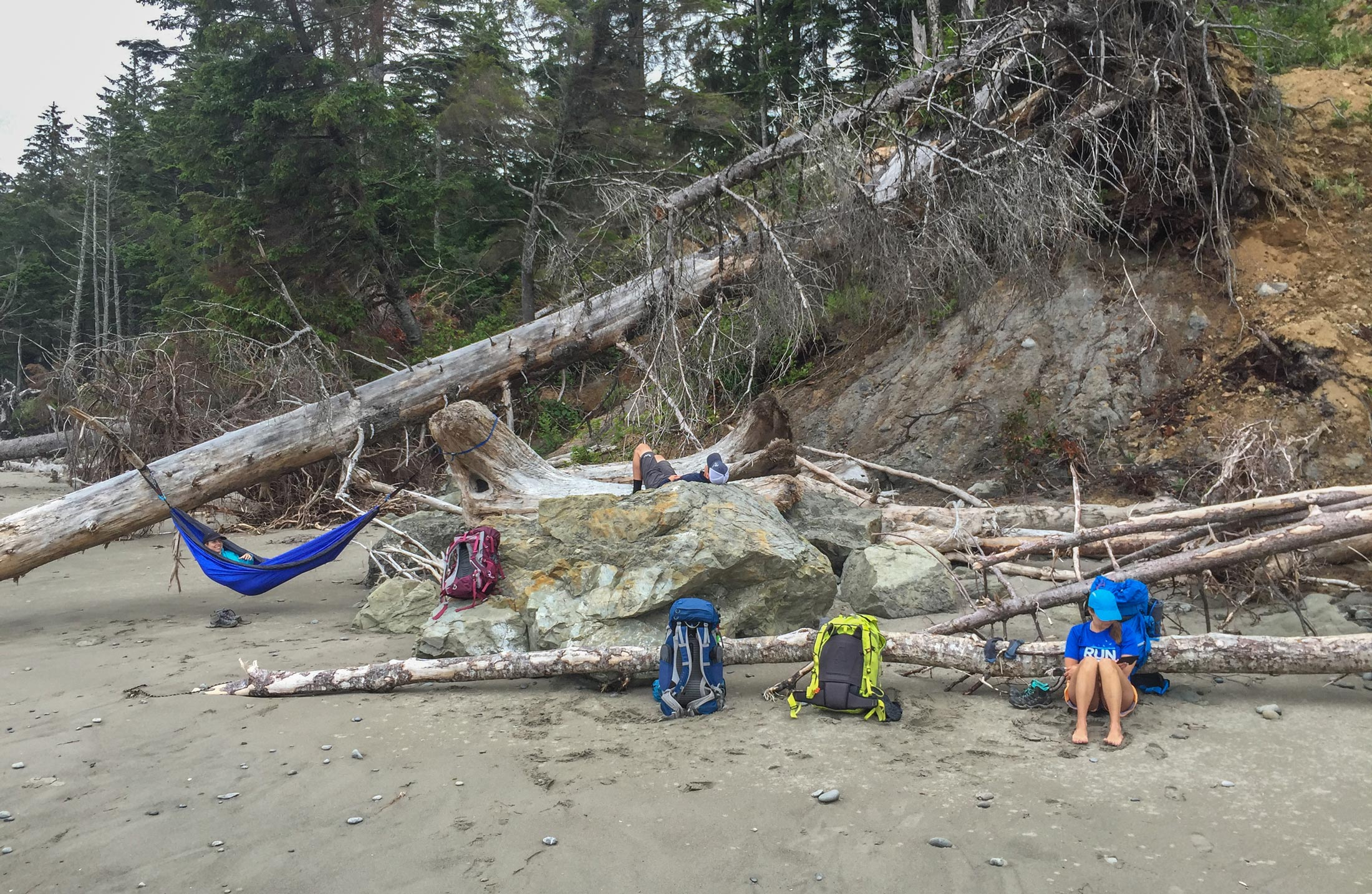 Backpackers wait for the tide to recede.